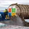 Un homme nettoie un grand cylindre blanc sur lequel apparaît le logo de Microsoft.