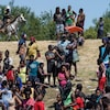 Des Haïtiens sur la rive du Rio Grande, surveillés par un policier à cheval.