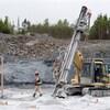Un travailleur marche sur le site de la mine d'or Touquoy en Nouvelle-Écosse à côté d'une machine.