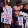 Des manifestants tiennent des pancartes avec des messages en anglais s'opposant à la mine Frontier.