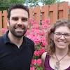 David Marra-Hurtubise et Annie Vanden Abeele, souriant, devant un parterre en fleurs clôturé.