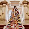 Une femme, de dos, porte une cape multicolore aux motifs autochtones.