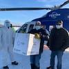 Dino Flett tient une grosse boîte dans les mains, il porte un masque et est entouré de deux hommes, dont un avec une visière médicale protectrice au visage. Les hommes se tiennent devant un hélicoptère.