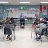 Une vingtaine d'élèves sont assis en classe devant leur enseignant.