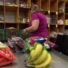 Une femme assise devant des étagères remplies de denrées alimentaires. Au premier plan, on voit des fruits et des légumes frais.
