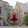 Une artiste de cirque en robe rouge se tient en équilibre dans un anneau géant.
