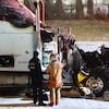 Un pompier et un policier examinent un camion calciné.