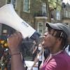 Un jeune homme crie dans un porte-voix parmi des manifestants qui portent des masques de protection et arborent une pancarte disant : Black Lives Matter.