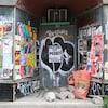 La devanture d'un commerce désaffecté est recouverte d'affiches et de graffitis.