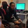 Une photo d'un jeune homme noir assis dans une chaise de bureau surdimensionnée et tenant une manette de jeu entre les mains.