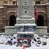 """Le monument commémoratif devant l'ancien hôtel de ville de Toronto entouré de gerbes de fleurs sous la neige sur lequel quelqu'un a écrit avec une bombe de peinture : """"Ye broke faith"""""""