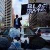 Un homme noir perché sur une voiture brandit un drapeau « Black Lives Matter ».