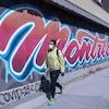 Un homme au manteau jaune portant un masque passe devant une murale sur laquelle est écrite le mot Montréal.