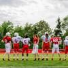 Sept joueurs et joueuses de football posent dos à la caméra sur un terrain de football.