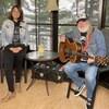 Une chanteuse sourit avec un guitariste.