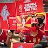 Les manifestants habillés de rouge portent des pancartes rédigées en anglais.