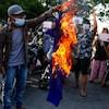 Un homme masqué tient un drapeau en feu sous le regard complice d'autres militants.