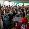 Des centaines de personnes sont réunies près d'un cercueil.