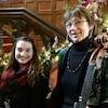 2 femmes souriantes sont debout à côté d'un escalier qui est tout décoré pour le temps des fêtes