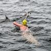 Une femme nage dans un lac avec des canards.