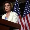 Nancy Pelosi parle dans un micro devant un lutrin. Derrière elle sont accrochés des drapeaux à l'effigie des États-Unis et de la Chambre des représentants.