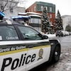 Une voiture de police devant un immeuble résidentiel.