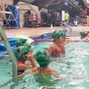 Huit enfants sont dans une piscine et apprennent à nager
