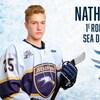 Nathan Drapeau affiche un air sérieux, avec son bâton de hockey dans les mains.