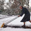 Un homme en peignoir pousse la neige dans son entrée avec une pelle.
