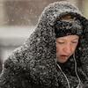 Une femme marche sous la neige.