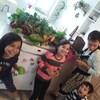 Nelcy Lopez et ses 3 enfants s'amusent dans leur cuisine. Des fruits et légumes sont posés sur le comptoir.