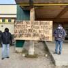 Deux hommes de chaque côté d'une pancarte sur laquelle est écrit « S'il vous plaît, plus de promesses brisées, assez c'est assez. »