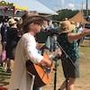 Des personnes danses et chantent, en compagnie d'une femme jouant de la guitare.