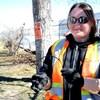 Jackie Tanner porte un gilet orange, des gants et des lunettes de soleil.