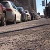 Un trottoir plein de roches côtoie une file de voitures stationnées.