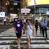 Des gens traversent une grande rue de New York en soirée. Ils portent presque tous le masque.