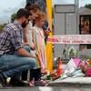 Les gens se recueillent devant un mémorial où des fleurs sont déposées.