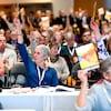 Des délégués du NPD assis ensemble dans une salle à Victoria tiennent des pancartes dans leurs mains.
