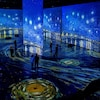 Des gens dans une salle où des toiles de Vincent Van Gogh sont projetées sur les murs et le plancher.