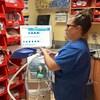 Une thérapeute respiratoire devant un respirateur.