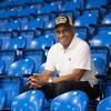 Willie O'Ree souriant est assis au milieu des gradins vides.