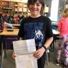 Le jeune Dean Humeny montre sa lettre à la caméra, dans sa salle de classe.