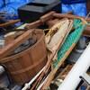 Plusieurs objets sont disposés pêle-mêle dont un panier et des raquettes.