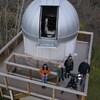 Des gens sur la plateforme de l'observatoire Hesje scrutent le ciel avec un télescope.