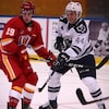 L'attaquant Drew Elliott du Drakkar de Baie-Comeau et le défenseur Anthony D'Amours de l'Océanic de Rimouski croisent le fer sur une patinoire.