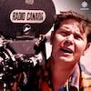 Le caméraman Robert Champagne, les yeux plissés, regarde une scène, sa caméra tout près de lui.