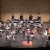 Les musiciens d'un orchestre jouent de leur instrument en portant un masque et en étant plus espacés les uns des autres qu'à l'habitude.