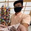 Deux hommes japonais posent devant une oeuvre de plusieurs origamis.