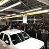 Un véhicule au premier plan, des employés dans une usine à l'arrière.