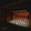 Des musiciens et musiciennes sur la scène d'une salle de spectacle vide.